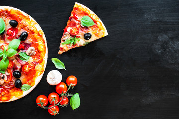 Ham, tomato and cheese  pizza on dark  background. Hot pizza with Pepperoni Sausage served at a pizzeria or restaurant