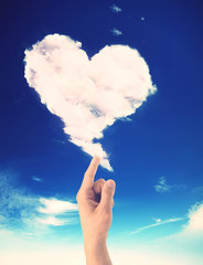 Hand drawing a heart shaped cloud over the blue sky. Valentine day concept