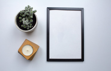 top view of photoframe on white table with plant decoration