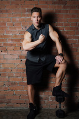 Muscular man Posing against a red brick wall. Standing In a checkered sleeveless shirt.