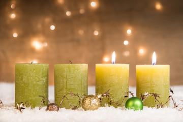 grüne adventskerzen im schnee zum 2. advent