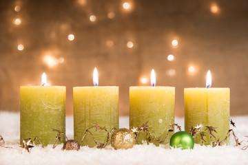 grüne adventskerzen im schnee zum 4. advent