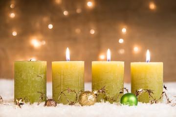 grüne adventskerzen im schnee zum 3. advent