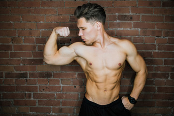 Young muscular bodybuilder fitness model posing against a brick wall loft fitness club. Beauty Ring flash.