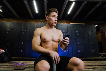 Young man at gym dressing room. Handsome guy at fitness studio doing their own staff before training.