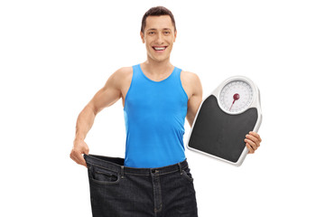 Guy in pair of oversized jeans holding a weight scale