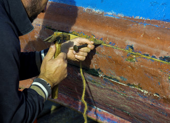 The sailor repairs his fishing boat by clogging the cracks in the timber with a cotton rope