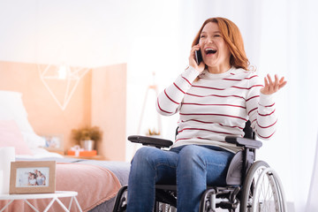 Great news. Joyful blond disabled woman smiling and talking on her phone while sitting in the wheelchair