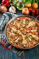 Traditional paella with chicken legs, sausage chorizo and vegeta