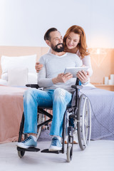 Have a look. Happy blond woman of middle age and a bearded disabled man smiling and the woman looking at the tablet while the she hugging him and standing behind him