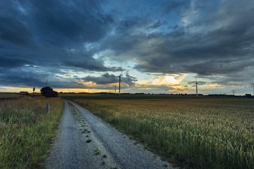 Wind turbines for electrical power generation in green agricultural fields in Normandy, France. Renewable energy sources, industrial agriculture concept. Environment friendly energy production