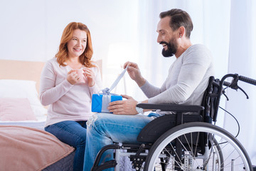 Opening the gift. Bearded disabled man opening a present while sitting in a wheelchair and a smiling woman sitting on the couch and holding a cup