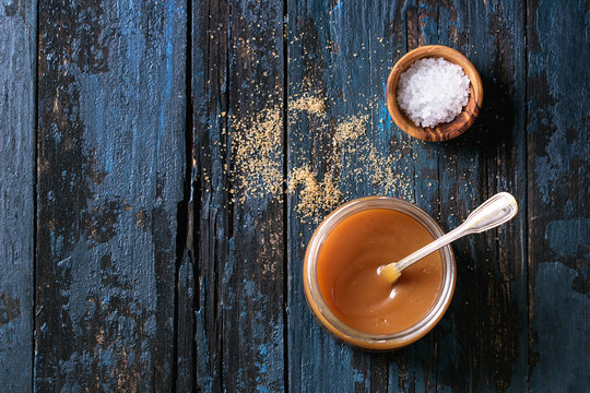Glass jar of homemade salted caramel sauce with spoon, brown sugar and bowl of salt. Over old dark blue wooden background. Top view with space