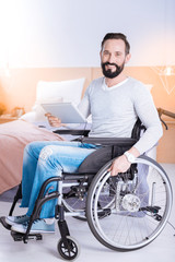 Enjoying life. Cheerful lovely bearded disabled man smiling and holding a tablet while sitting in a wheelchair