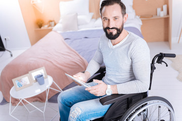 Using gadget. Inspired smiling bearded disabled man wearing jeans and a sweater and holding a tablet while sitting in a wheelchair