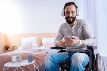 Listening to music. Gleeful bearded dark-haired handicapped man of middle age smiling and wearing headset and holding a phone while sitting in a wheelchair