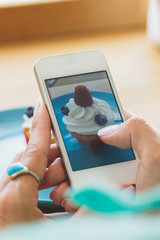 Woman takes a picture of cupcake on the plate