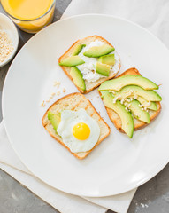 Breakfast. Eggs on toast with avocado, soft white cheese, spices and nuts. White plate, gray concrete background.