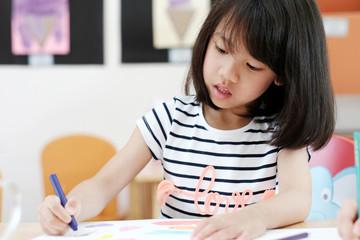 Asian girl drawing color pencils in kindergarten classroom, preschool and kid education concept