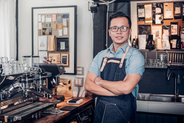 Male Barista cafe owner cross arms in store counter bar inside coffee shop, food and drink business start up