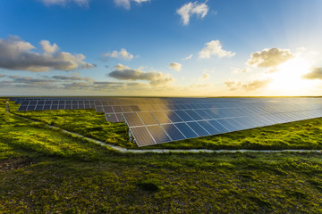 Solar panels at sunrise with dramatic cloudy sky in Normandy, France. Modern electric power...