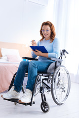 Working at home. Exuberant smiling blond handicapped woman of middle age wearing glasses and writing on a sheet of paper while sitting in a wheelchair in a blue sweater