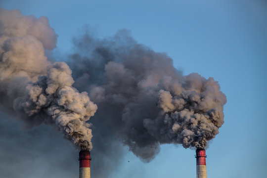 industrial chimneys with heavy smoke causing pollution on the blue sky background