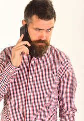 Guy in plaid shirt talks on mobile phone.