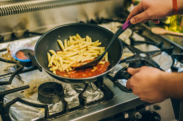 Chef cook prepares the pasta and spaghetti in frying pan