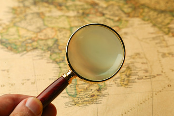 hand holding a magnifier on vintage map