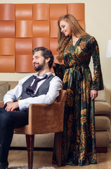 Picture of elegant businessman on chair and long-haired woman in dress
