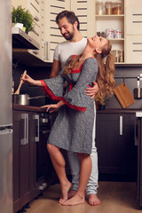 Photo of happy loving couple preparing food in kitchen