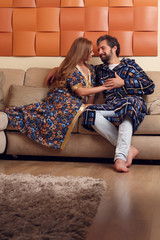 Picture of women and men in home clothes hugging on sofa