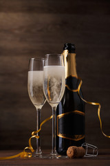 Picture of two wine glasses with sparkling champagne, bottle, cork
