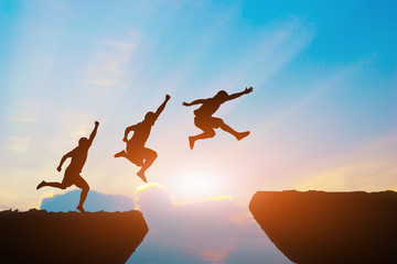 Men jump cliff sun light over silhouette