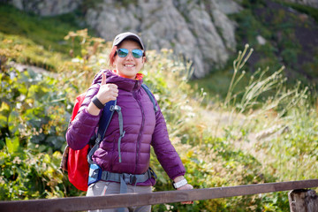 Female tourist in sunglasses against of picturesque mountains