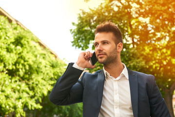 Young businessman talking on a phone on the sunny street
