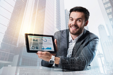Positive manager. Positive smart cheerful manager showing important information on the screen of his tablet while sitting at the table