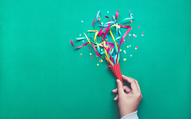 Celebration,party backgrounds concepts ideas with hand holding colorful confetti,streamers.Flat lay