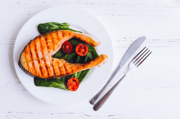 Grilled salmon steak with tomatoes cherry and spinach