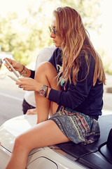 Young blond women in black sunglasses sitting in the cabriolet and holding her phone in hands.