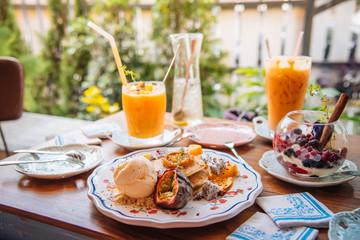 Sweet Pancakes with honey and vanilla ice cream Fruit with Orange focus on pancake