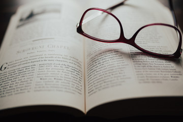 Red glasses sitting on book