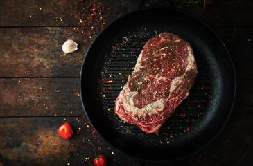 Raw fresh ribeye steak with salt, seasonings, and rosemary in a frying pan