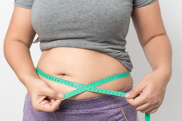 Overweight woman check out his body fat with green measuring tape for obesity on gray background, Healthy concept