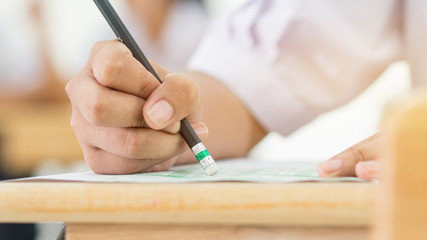 Students holding pencil eraser while taking exams, examination room, writing answer optical form in high school classroom, view of having test in class on seat rows, Education  literacy concept.