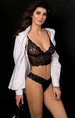 Beautiful sexy girl in black lingerie in a white shirt. Young model in photo studio on a black background. Advertising of underwear. Big breasts. Perfect skin.