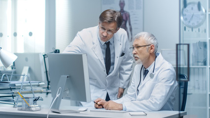 Senior Doctor and His Assistant Discuss Patient's Log on Personal Computer.