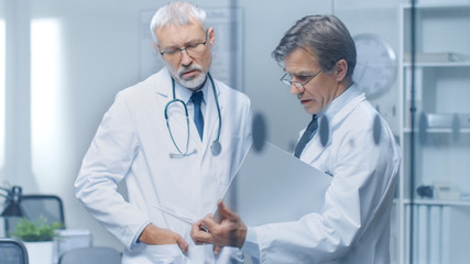 Two Specialist Doctors Discussing Patient's Log. Both are Senior and Experienced. Their Office Looks Modern and Respectable.