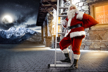 The old Santa Claus in a red costume walks up the silver ladder. Old house in the mountains with many windows and orange light. Landscape of winter mountains with huge moon in the sky.